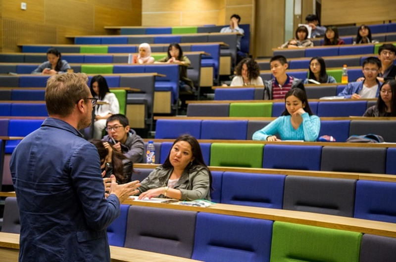 Medium pre sessional english students and teacher in a lecture theatre